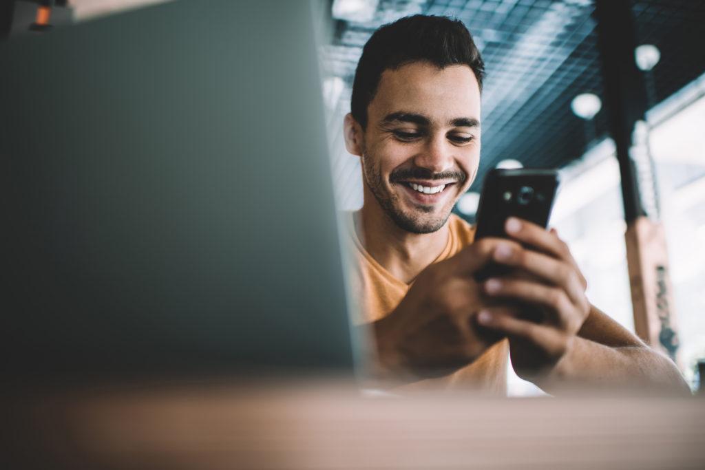 Jeune homme souriant téléphone portable smartphone newsletter information